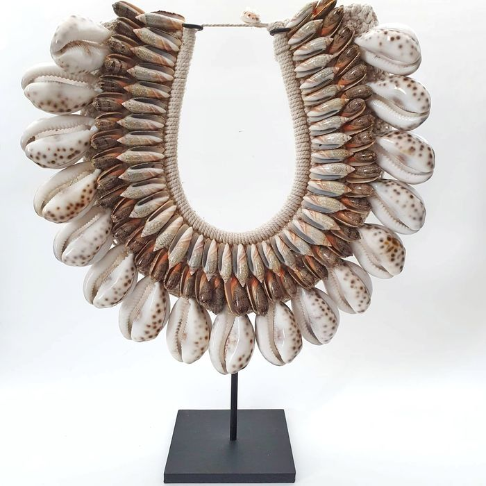 Decorative necklace on blackened metal stand (1) - Big tiger kauri shells  mixed with other shells stitched on natural fibers
