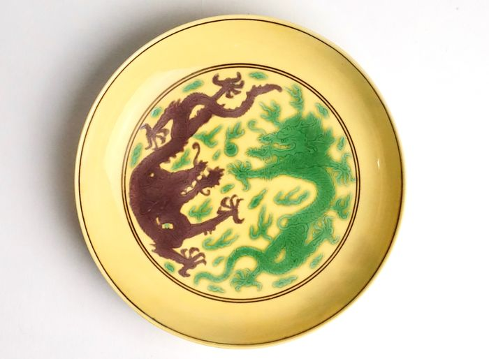 Piatto - Porcellana - An Imperial Green And Aubergine-Glazed Yellow-Ground Dish, Kangxi Mark And Of The Period - Cina - Kangxi (1662-1722)