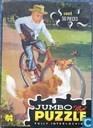 Jongen op fiets met hond ervoor
